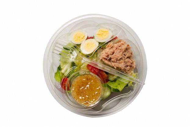Salade de thon frais avec laitue, concombres, cerises et œufs dans un récipient en plastique. vue de dessus.
