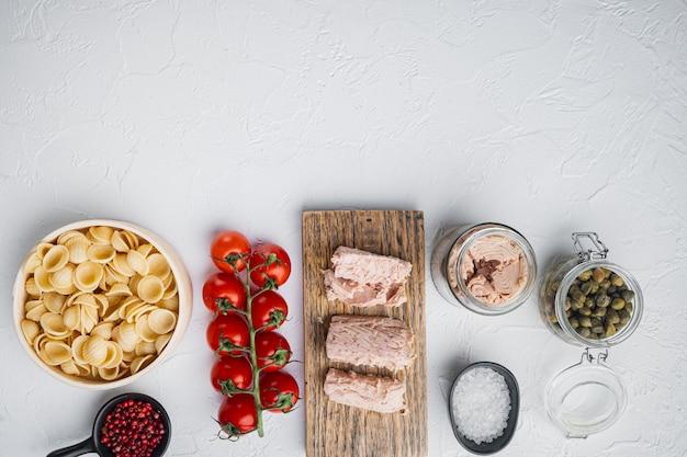 Salade de thon avec des ingrédients de pâtes et légumes sur blanc, vue du dessus