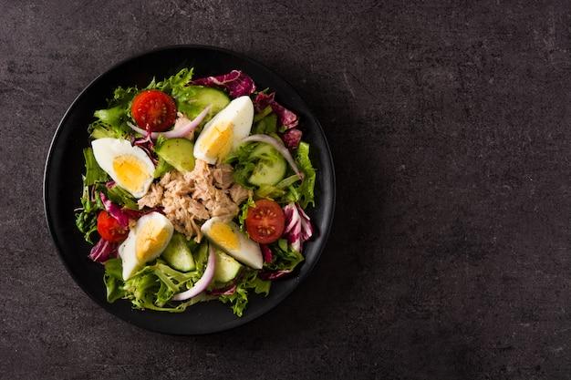Salade de thon, oeuf et légumes sur fond noir