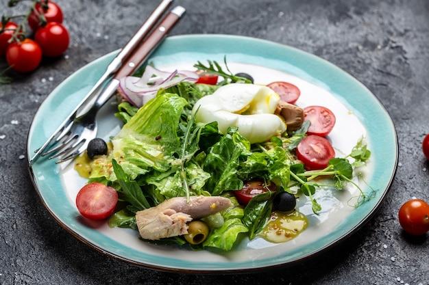 Salade de thon avec oeuf poché, laitue, cerise, tomates olives et maïs