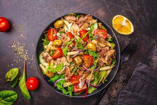 Salade de thon avec pâtes, olives et légumes dans une assiette noire
