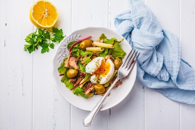Salade de thon avec pâtes, olives et œuf poché dans une assiette blanche sur du bois blanc