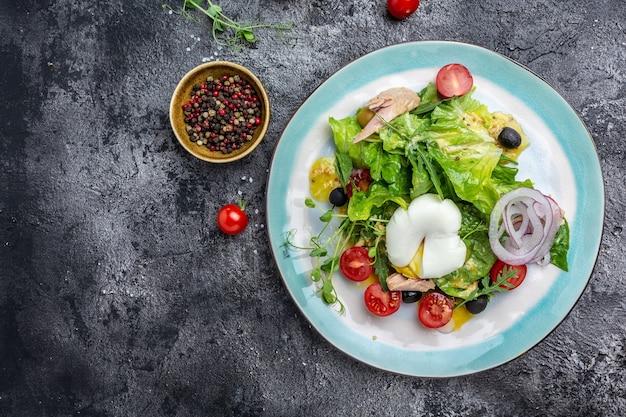 Salade de thon poché, œuf, laitue, cerise, tomates, olives et maïs sur fond pierre sombre ou béton. vue de dessus. espace de copie.