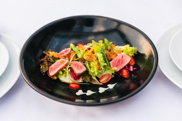 Salade de thon rare (corail vert, corail rouge, œufs de saumon et tomates) avec oursin touché dans une assiette noire.