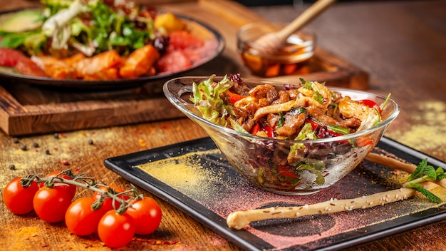 Salade tiède au bœuf et poulet, poivrons et sauce miel et menthe.