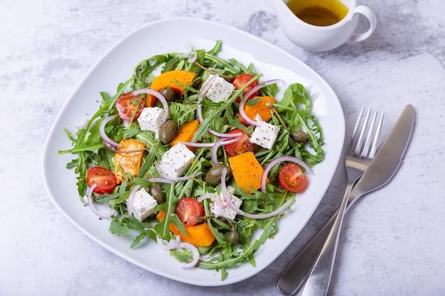 Salade tiède avec potiron, fromage feta, tomates, câpres, roquette et oignon rouge. fermer.