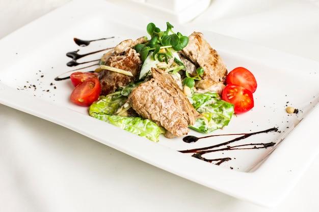 Salade tiède avec viande, champignons, tomates cerises, pignons et herbes