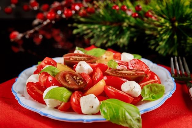 Salade de tomate, fromage mozarella et basilic. plat végétarien pour le nouvel an ou noël.