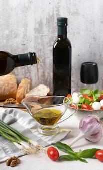 Salade tomate mozzarella feuilles de basilic olives noires et huile d'olive sur table en bois