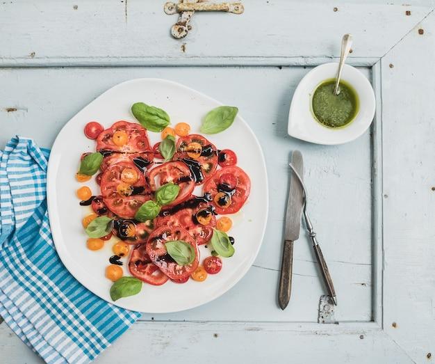 Salade de tomates anciennes village avec de l'huile d'olive et du basilic sur fond en bois bleu clair