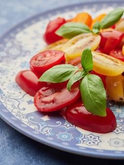 Salade de tomates cerises colorées garnie de feuilles de basilic sur une plaque bleue, vue en gros