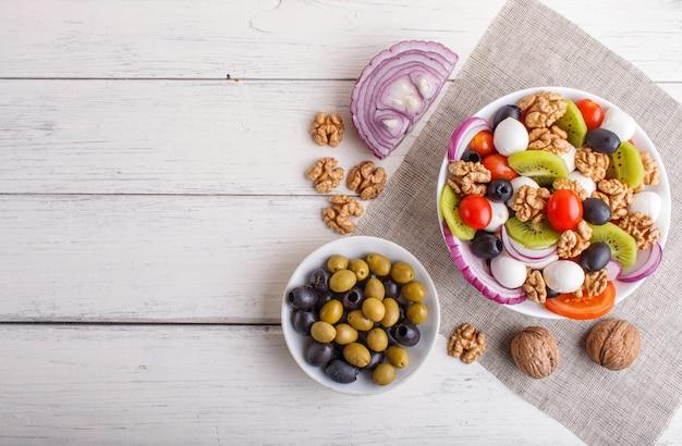 Salade de tomates cerises, fromage mozzarella, olives, kiwi et noix sur une surface en bois blanche.