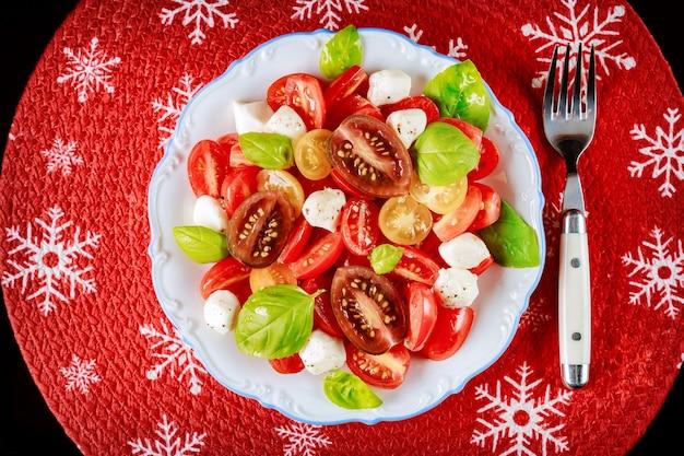 Salade de tomates cerises et mozzarella à la fourchette pour le dîner de noël. plat végétarien.