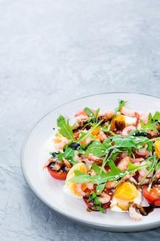 Salade de tomates cerises, œufs, crevettes cuites, roquette, graines de sésame et sauce balsamique dans une assiette sur la table
