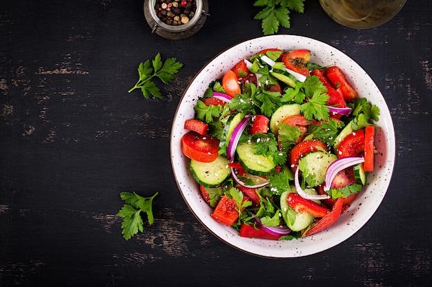 Salade de tomates et concombres à l'oignon rouge, paprika, poivre noir et persil. nourriture végétalienne. menu diététique. vue de dessus. mise à plat