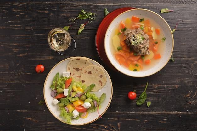 Salade de tomates, concombres, poivrons, olives et fromage feta. salade grecque. dans une assiette d'argile blanche sur une table en bois
