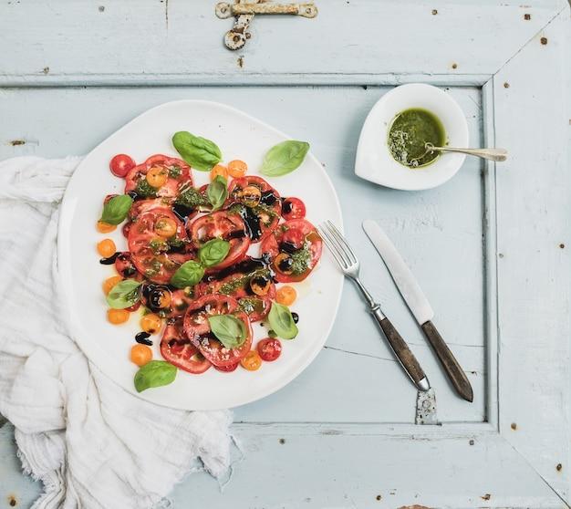 Salade de tomates héritage du village mûr avec de l'huile d'olive et du basilic sur une planche en bois bleu clair