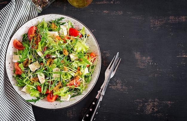 Salade de tomates avec un mélange de micro-légumes verts et de camembert. vue de dessus