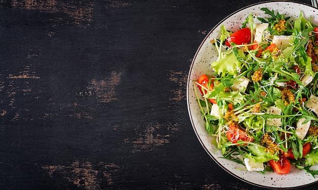 Salade de tomates avec mélange de micro-verts et de camembert.