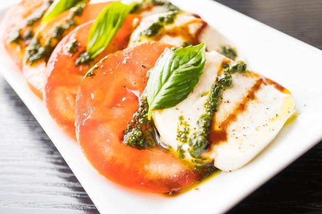 Salade de tomates et mozzarella dans une assiette blanche