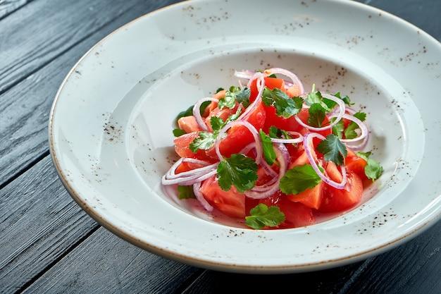 Salade de tomates et oignons, huile d'olive dans une assiette blanche sur table en bois
