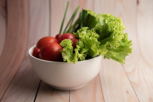 Salade de tomates et oignons de printemps dans une tasse blanche sur un plancher en bois.