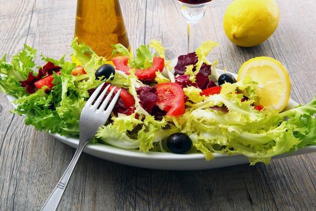 Salade de tomates et d'olives sur une table en bois