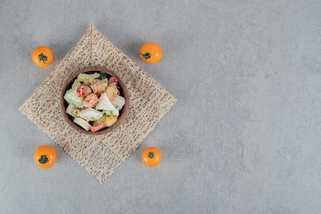 Salade de tomates vertes hachées aux herbes et épices sur une surface en béton