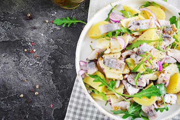 Salade traditionnelle de filet de hareng salé, pommes fraîches, oignons rouges et pommes de terre.