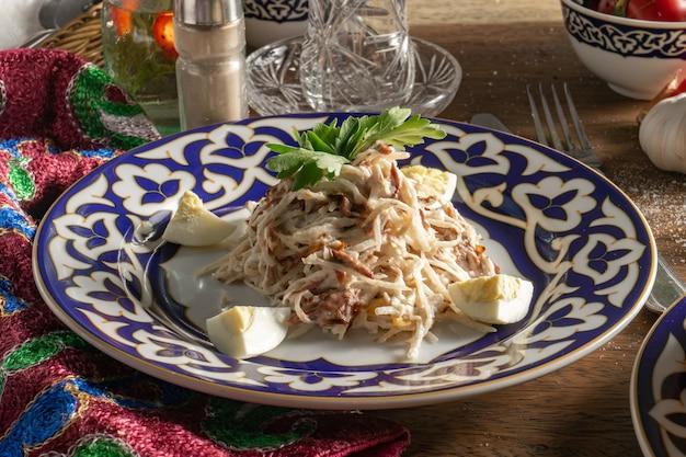 Salade traditionnelle ouzbek de tachkent de boeuf, radis daikon et oignon frit, œuf à la coque et persil avec sauce mayonnaise dans une assiette en céramique avec des ornements traditionnels ouzbeks sur une table en bois.