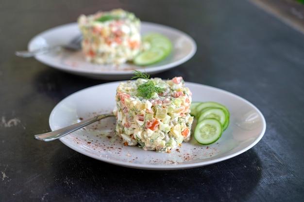 Salade traditionnelle russe faite maison saine olivier prête à manger dans l'assiette, gros plan
