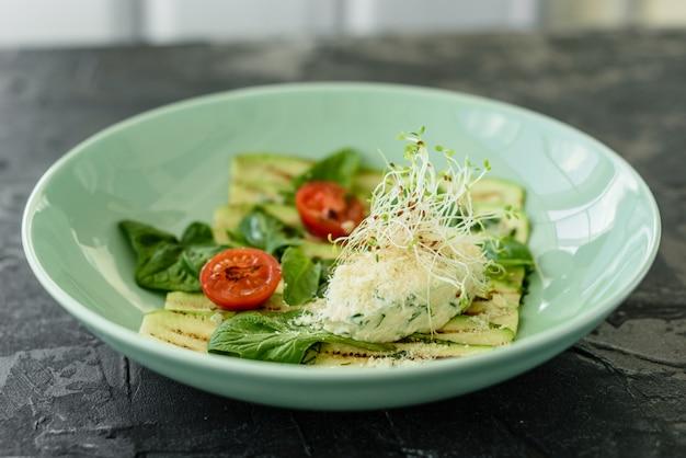 Salade de tranches de courgettes à la tomate cerise, fromage à la crème et micro verts. la nourriture végétarienne
