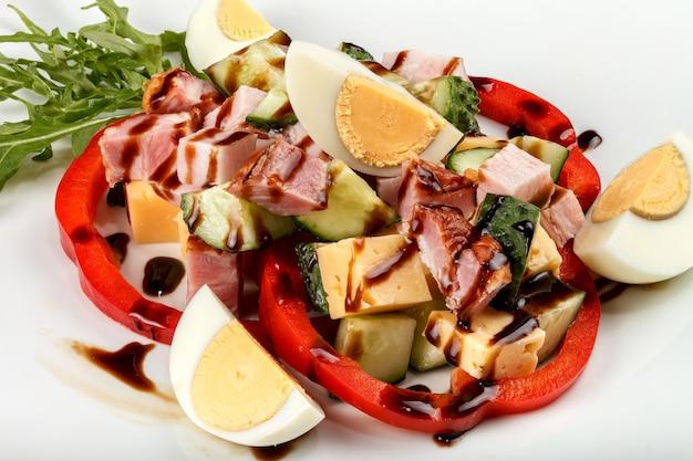 Salade en tranches avec jambon, concombre, fromage, œufs et poivron.