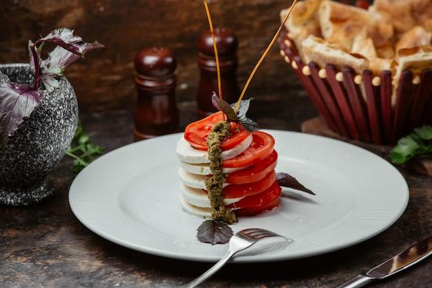 Salade avec des tranches de mozarella et de tomates avec vinaigrette au basilic et aux herbes.