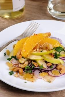 Salade avec tranches d'orange, pomme, oignon bleu, raisin sec, noix, noix de cajou, herbes et sauce au miel