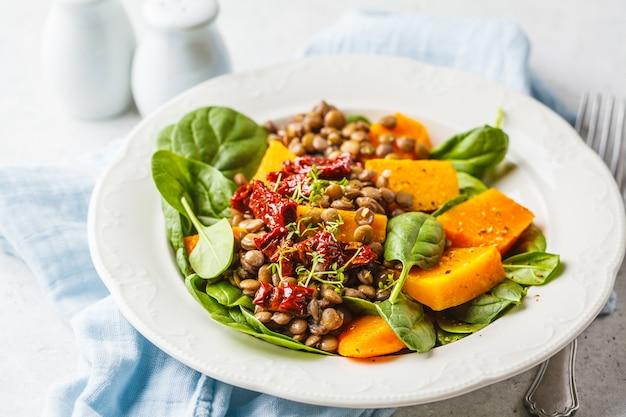 Salade végétalienne aux lentilles, citrouille et tomates séchées dans une assiette blanche.