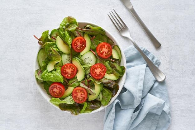 Salade végétalienne aux tomates, concombres, avocat sur table en béton gris pastel.