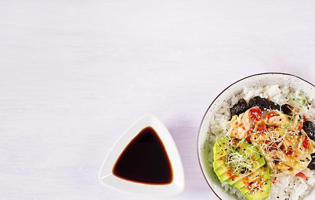 Salade végétalienne avec riz, chou kimchi mariné, avocat, nori et sésame sur bol.