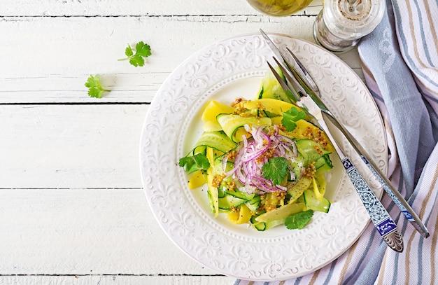 Salade végétalienne saine mangue, concombre, coriandre et oignon rouge dans une sauce aigre-douce. nourriture thaï. repas sain. . mise à plat
