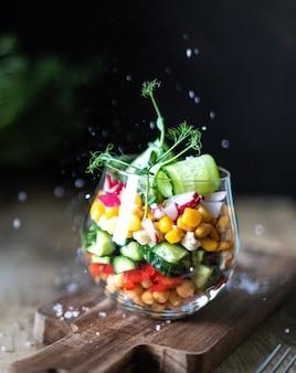 Salade végétarienne arc-en-ciel dans une tasse en verre sur un fond en bois. nutrition adéquat. copiez l'espace. verticale. sombre