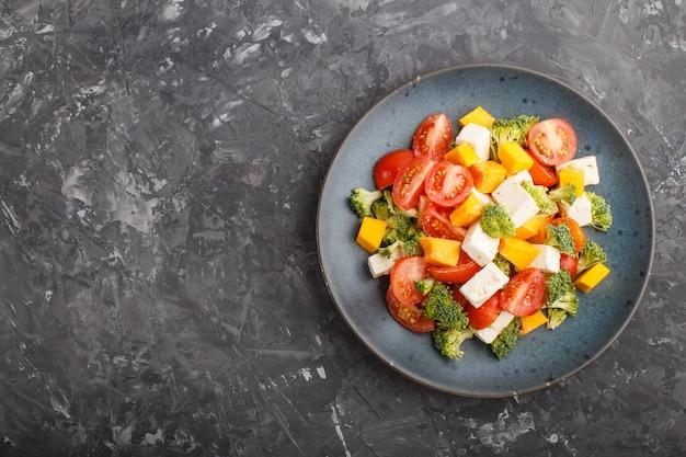 Salade végétarienne au brocoli, tomates, fromage feta et citrouille sur une assiette en céramique bleue