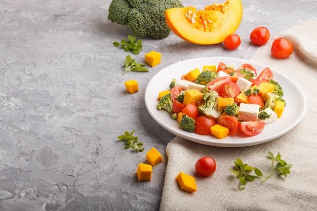 Salade végétarienne au brocoli, tomates, fromage feta et citrouille sur une plaque en céramique blanche