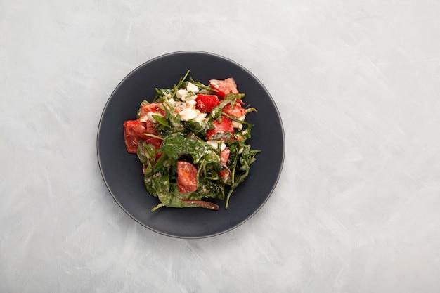 Salade végétarienne aux tomates roquette et fromage végétalien assaisonné de vinaigre balsamique