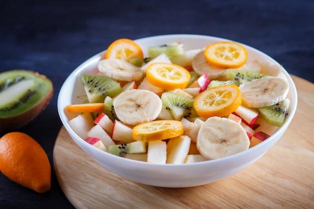 Salade végétarienne de bananes, pommes, poires, kumquats et kiwis sur bois noir