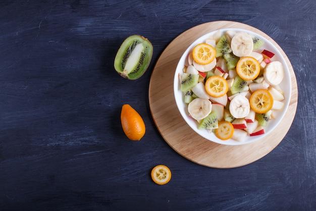 Salade végétarienne de bananes, pommes, poires, kumquats et kiwis sur fond noir en bois.