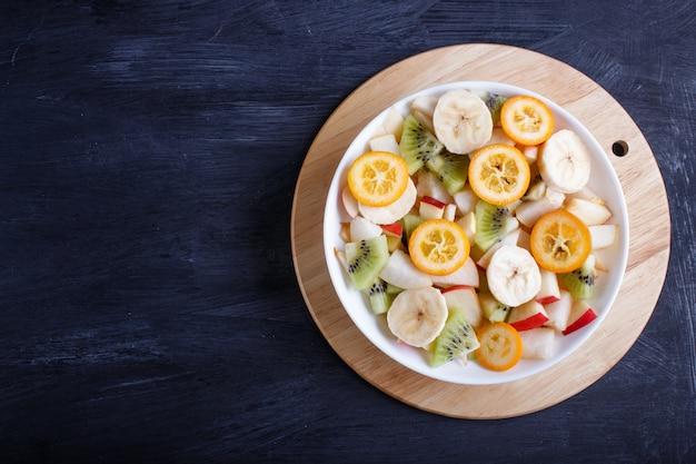 Salade végétarienne de bananes, pommes, poires, kumquats et kiwis sur une table en bois noire.