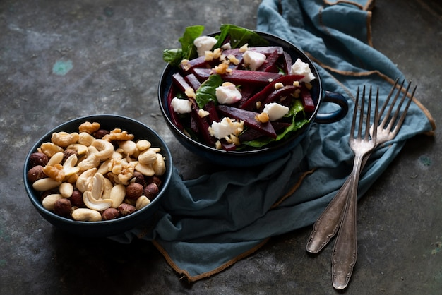 Salade végétarienne de betteraves aux épinards, fromage de chèvre et noix diverses. régime alimentaire, sain, collation, concept de repas de déjeuner. sur fond rustique.