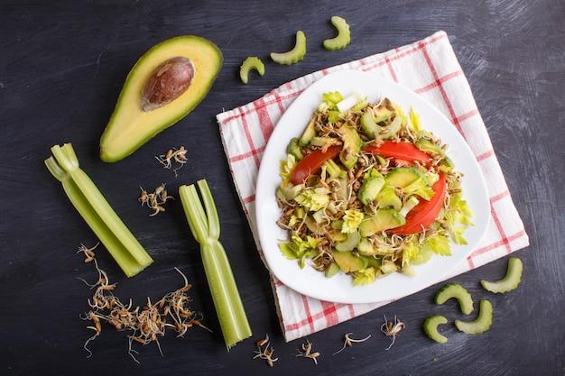 Salade végétarienne de céleri, seigle germé, tomates et avocat sur une nappe en lin, vue de dessus, sur fond noir.