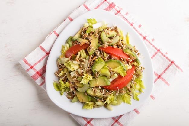 Salade végétarienne de céleri, seigle germé, tomates et avocat sur une nappe en lin, vue de dessus.
