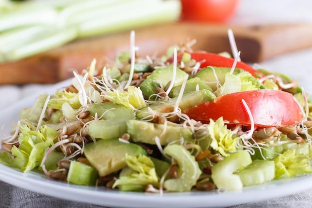 Salade végétarienne de céleri, seigle germé, tomates et avocat sur nappe en lin.